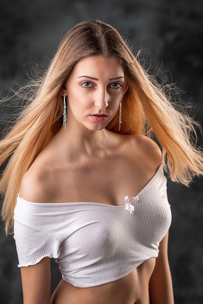 Junge Frau mit weissem Oberteil und langen Haaren blickt direkt in die Kamera
