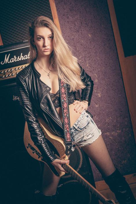 Mädchen mit E-Gitarre vor einem Marshal-Amp